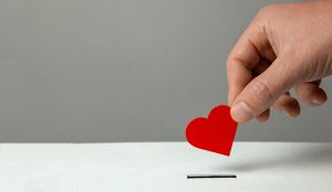 Hand putting a heart shaped card in a box