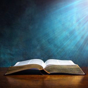 Open bible with light beams